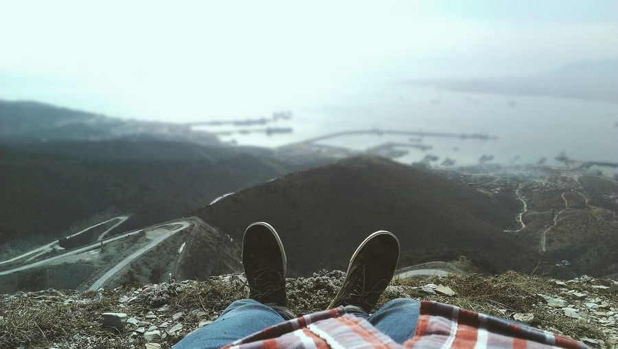 Close-up of legs against scenic background