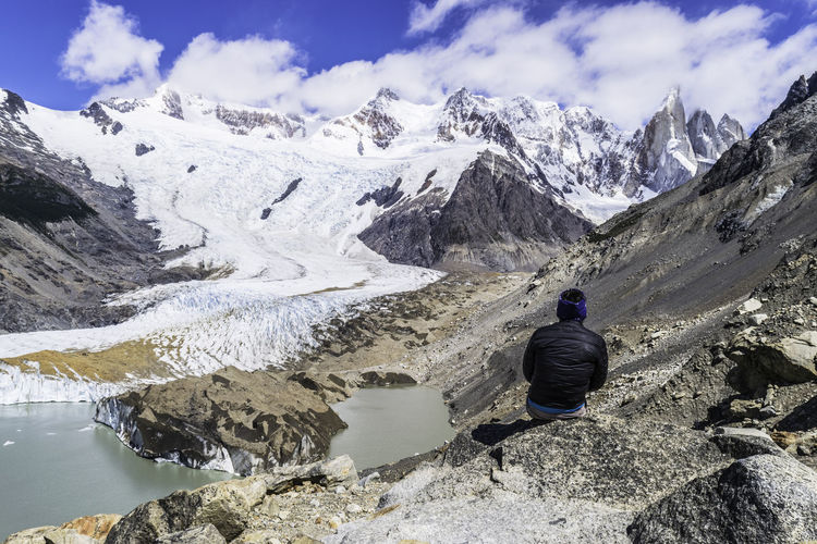 Rear view of person sitting on rock against snowcapped mountain range