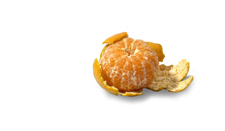 Close-up of fresh orange fruit against white background