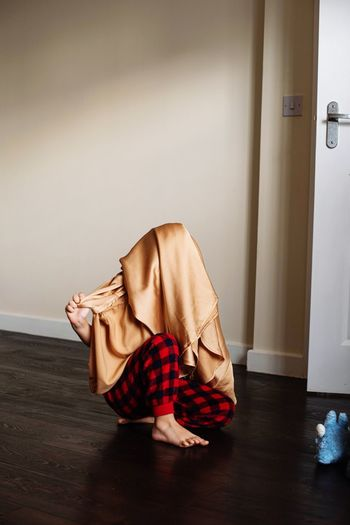 Woman covering face while sitting on wooden floor at home