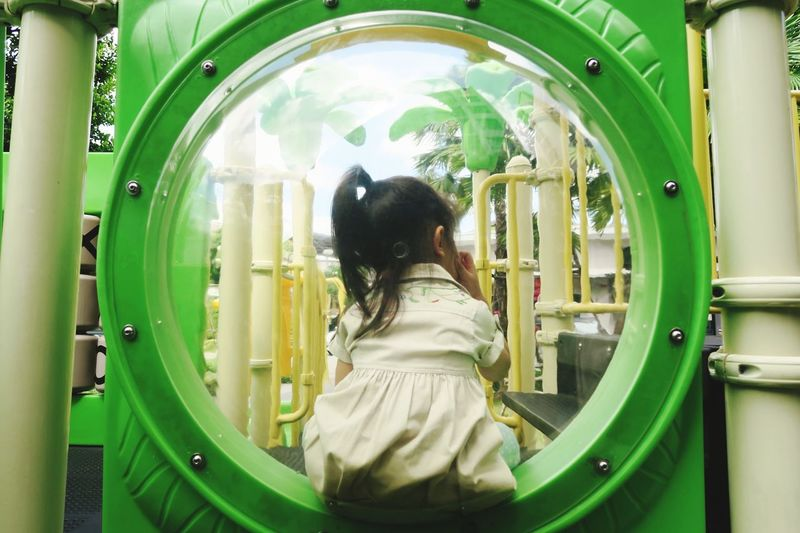 Rear view of asian girl sitting in playground