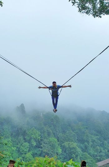 A man swing in the sky by rope