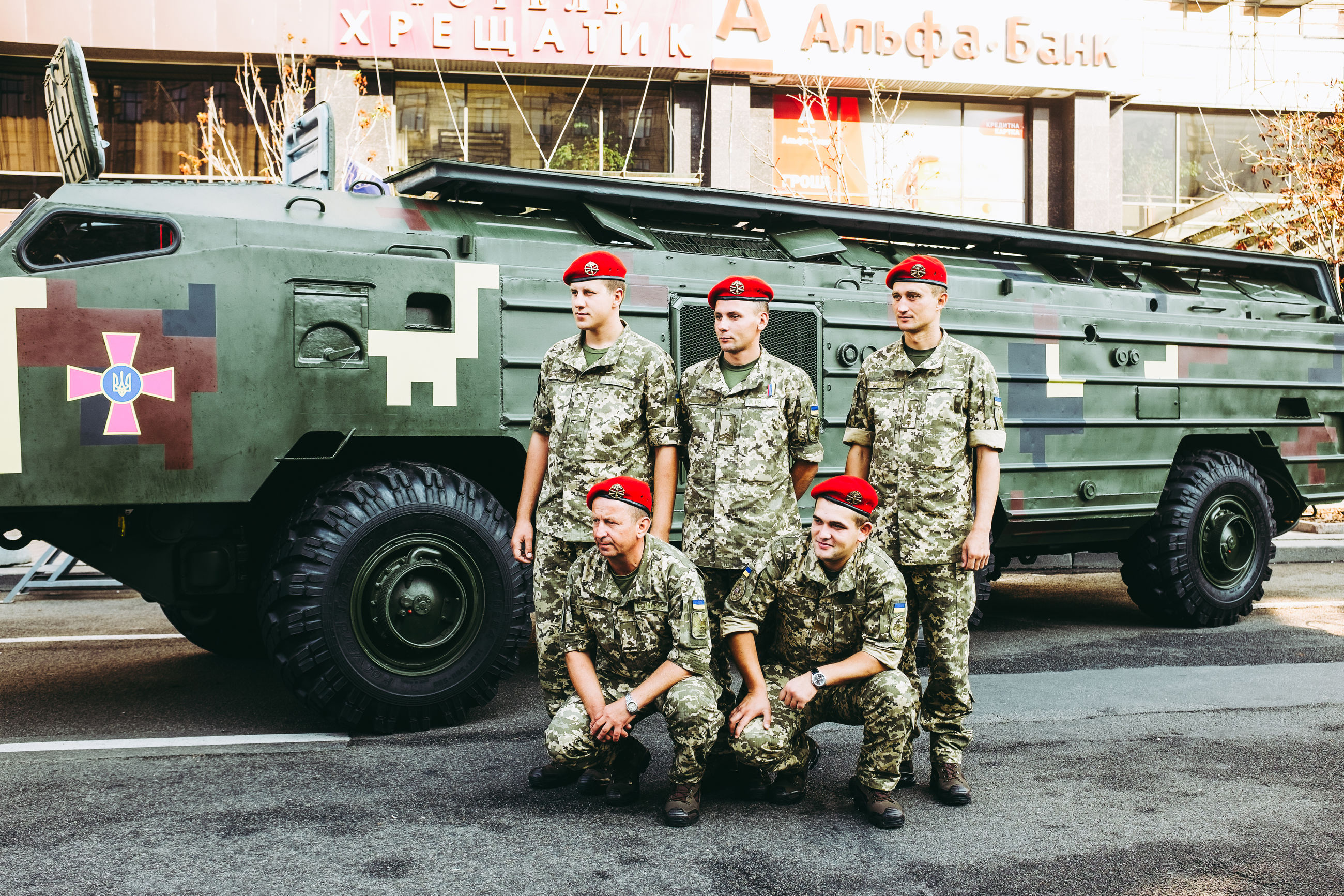 uniform, military uniform, army soldier, army, heroes, military, camouflage clothing, transportation, real people, men, armed forces, standing, young adult, patriotism, day, cap, looking at camera, full length, outdoors, mode of transport, courage, road, protection, portrait, occupation, responsibility, young men, land vehicle, stationary, pride, young women, teamwork, building exterior, one person, adult, people