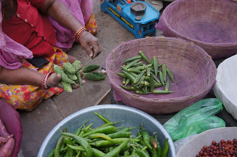 Low section of woman selling vegetables at market