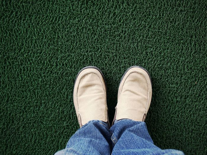 Low section of man standing on doormat