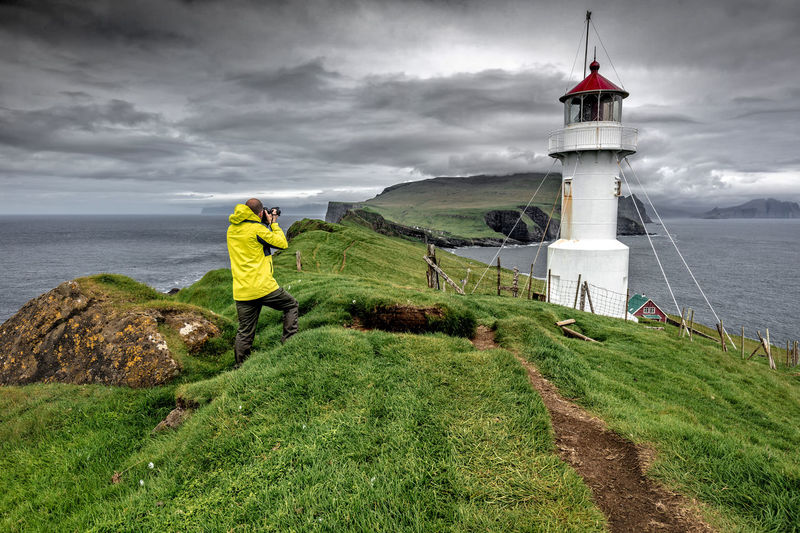 Man photographing lighthouse while standing at beach against cloudy sky