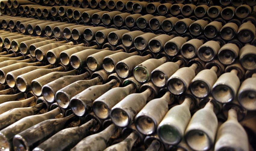 Full frame shot of dust covered wine bottles in warehouse