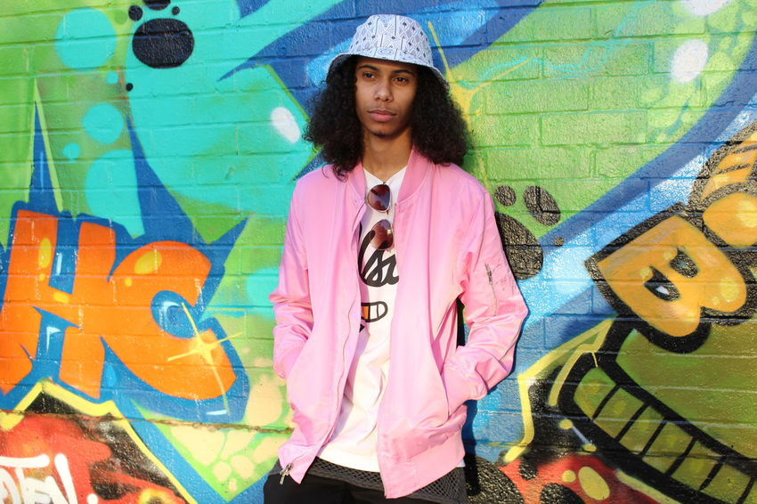 Graffiti Street Art One Person Portrait Fashion Attitude Adults Only Individuality Front View Adult Standing Looking At Camera Cool Attitude People Young AdultHuman Body Part Confidence  Pink Color Only Men Hanging One Man Only Outdoors Lifestyles Day Multi Colored