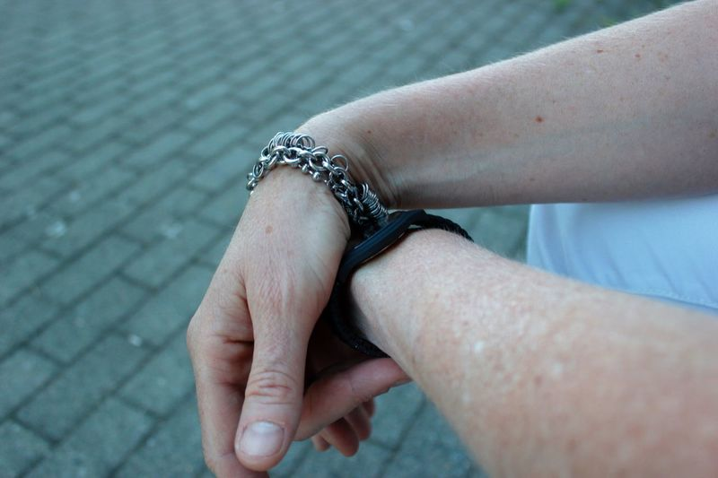 Cropped hand of man wearing bracelet on footpath