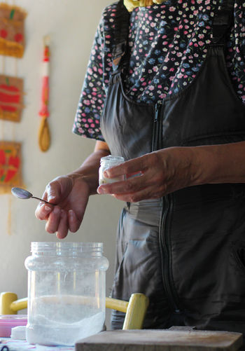 Midsection of woman holding salt bottle while standing by table in kitchen