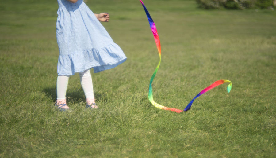 Low section of girl playing with ribbon on field