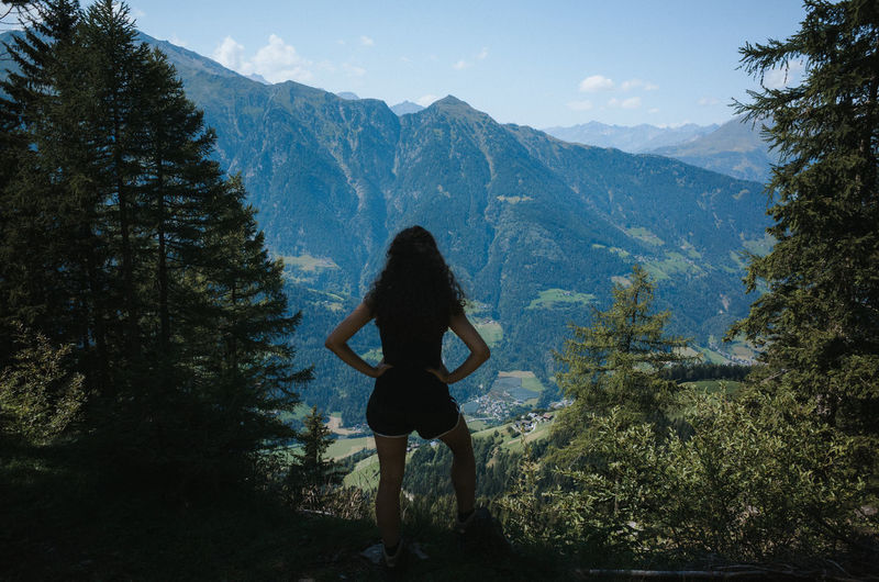 Rear view of woman standing in forest against mountain
