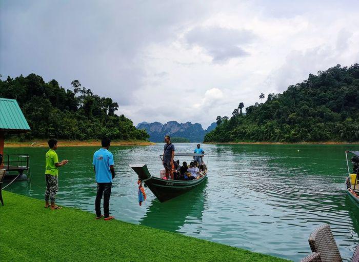 People on riverbank against sky