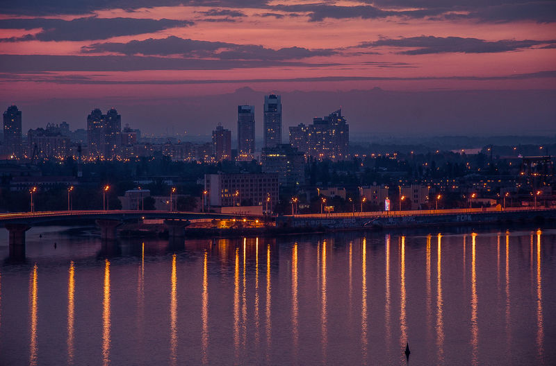 Illuminated buildings by river against romantic sky at sunset