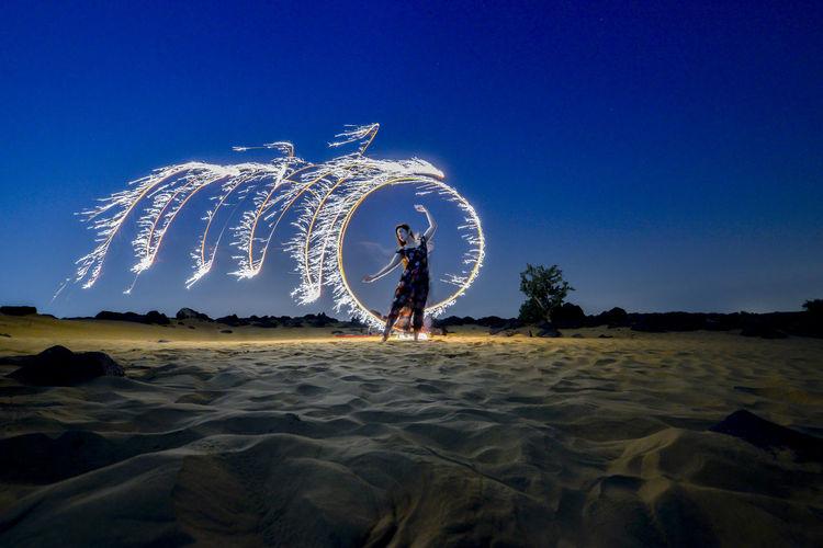 Full length of illuminated ferris wheel against sky