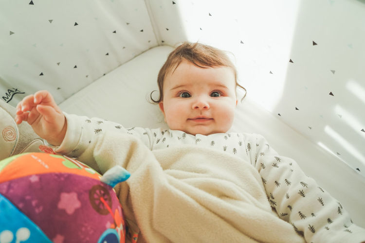 Directly above shot of cute baby girl lying on bed at home