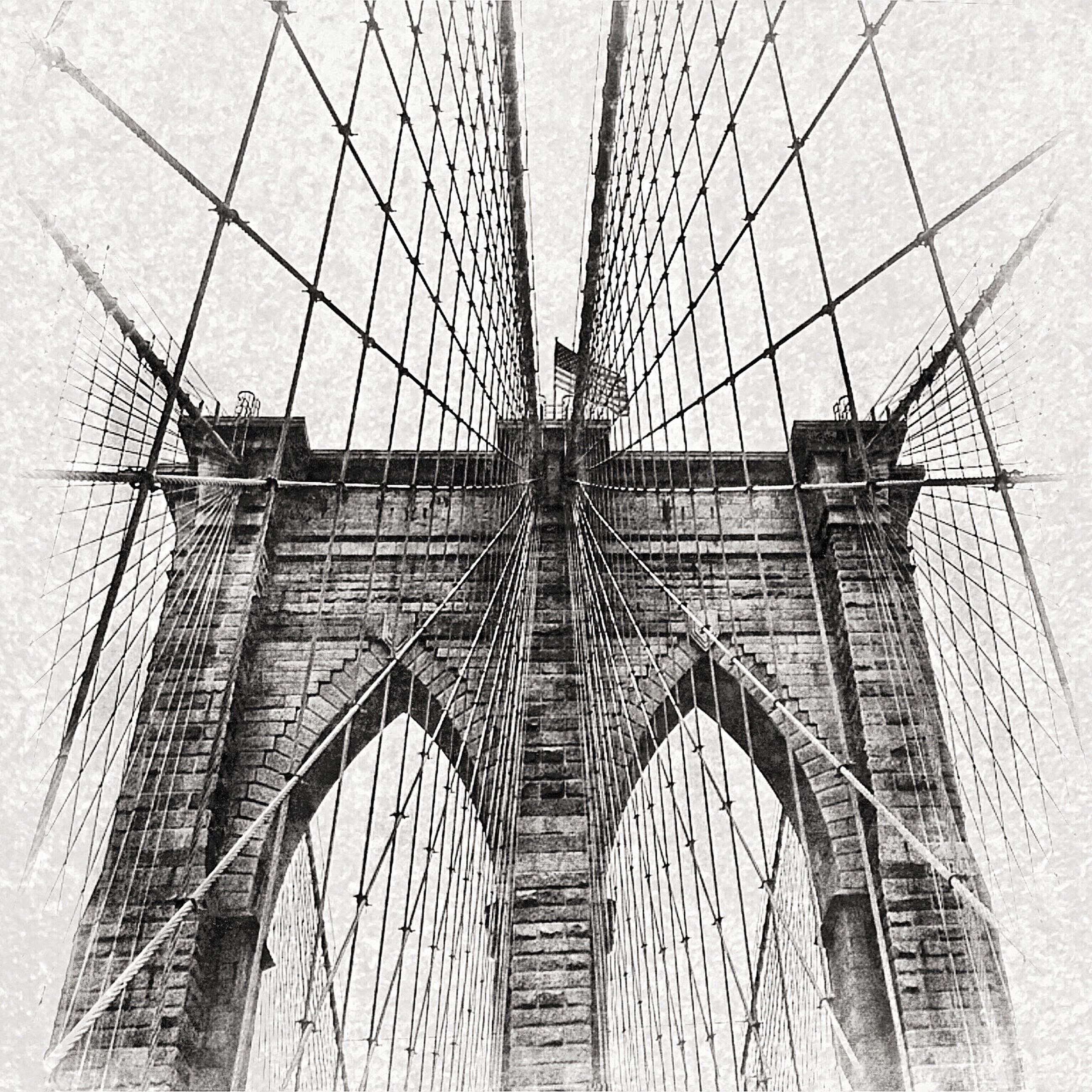 architecture, built structure, building exterior, low angle view, connection, tall - high, city, modern, international landmark, famous place, travel destinations, clear sky, skyscraper, capital cities, engineering, tower, bridge - man made structure, day, sky, suspension bridge