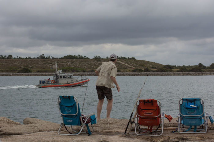 Coast Guard & fisherman Adults Only Casual Clothing Cloud - Sky Coast Guard Boat Fisherman Jetty Park Jetty View One Person Outdoors Port Canaveral Real People Rear View Sand Three Chairs