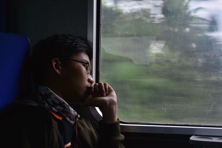 A man looking through train window