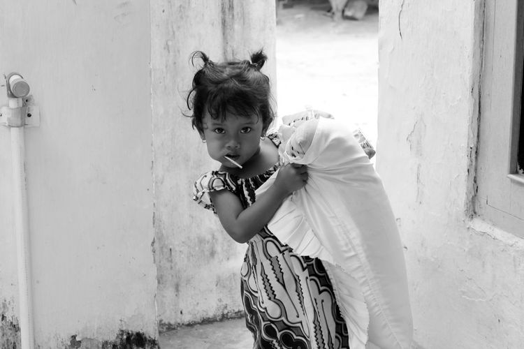 Portrait of girl having lollipop and carrying pillow against built structure
