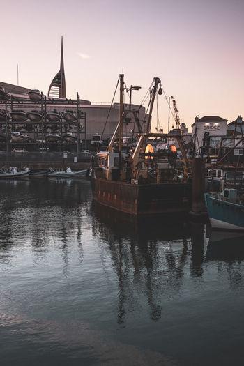 Sailboats in harbor at sunset
