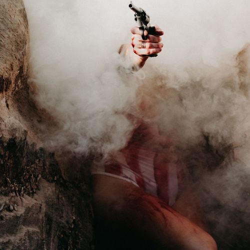 Midsection of mid adult woman holding handgun amidst smoke