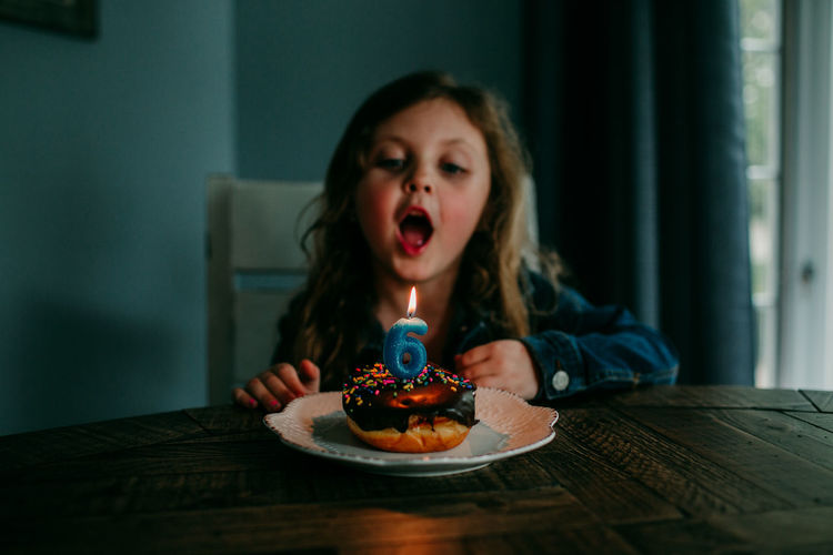 Cute girl blowing candle on birthday cake