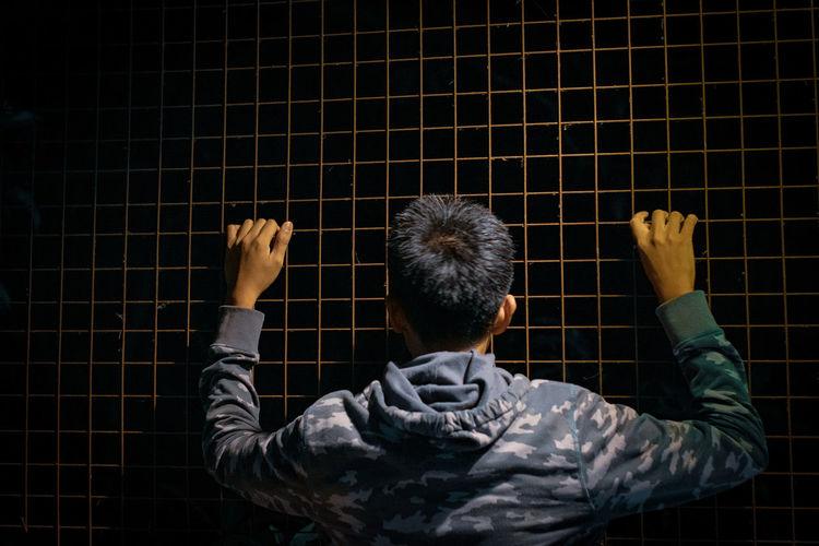 Rear view of man holding fence