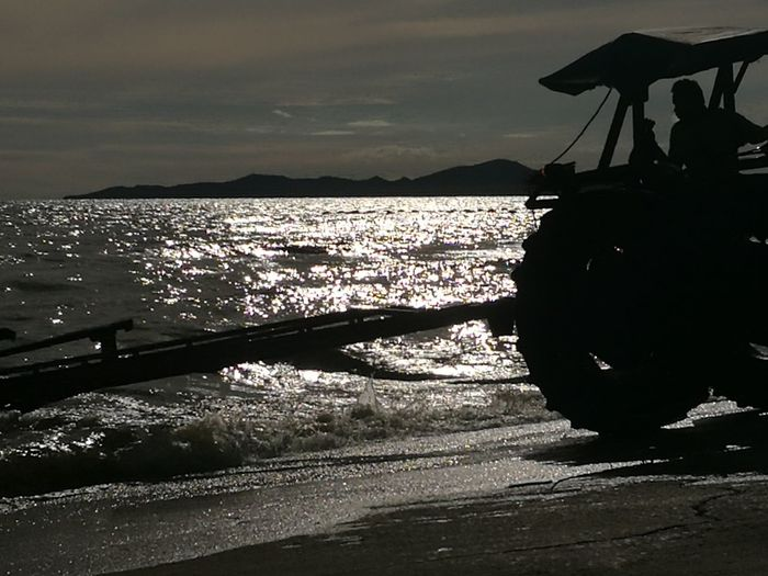 Silhouette vehicle on shore against sky