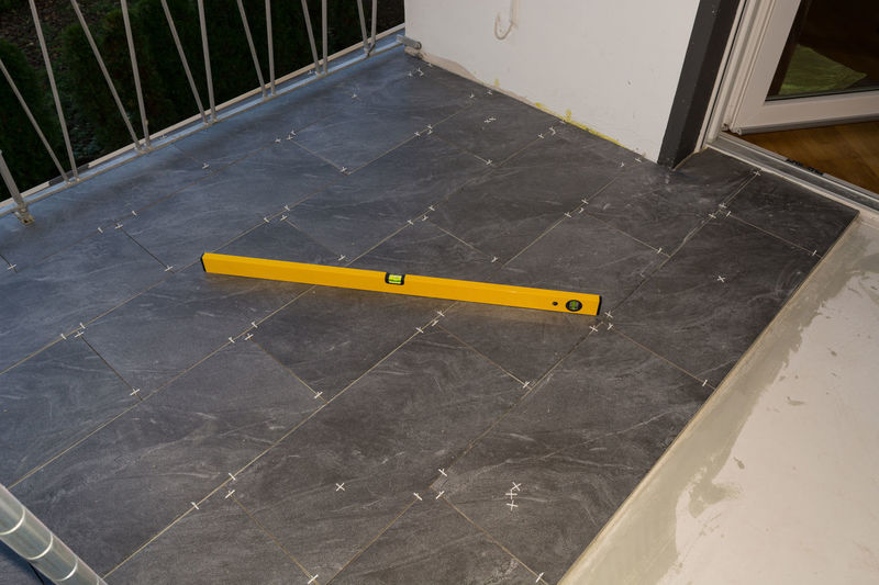 Balcony floor tiles installation. Laying tiles from porcelain. Interior remodeling theme. Yellow High Angle View No People Sign Day Communication Outdoors Architecture Railing Barrier Entrance Boundary Number Metal Fence Nature Text Empty Safety Door #NotYourCliche Love Letter Humanity Meets Technology