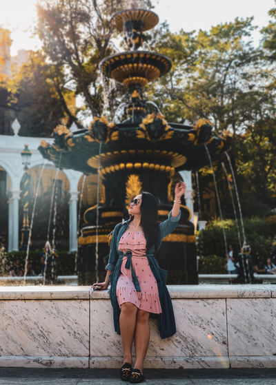Full length of woman standing against fountain in park