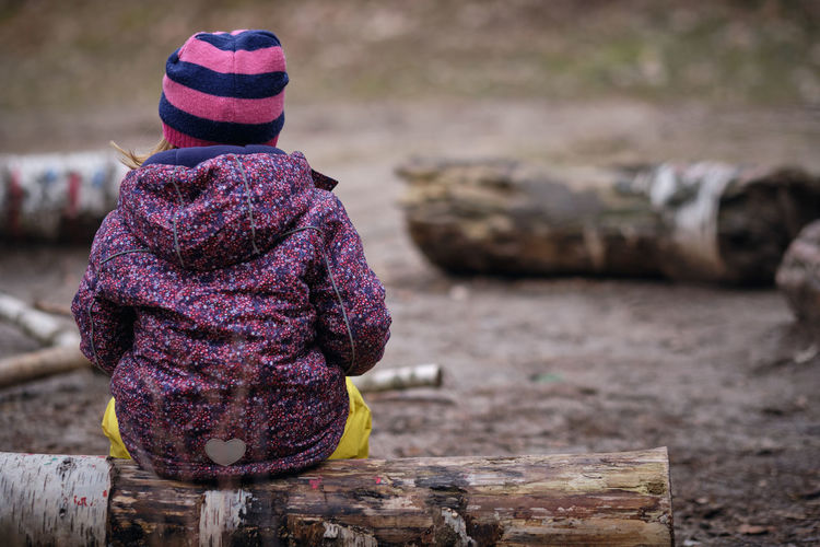 Rear view of girl sitting on wood in forest