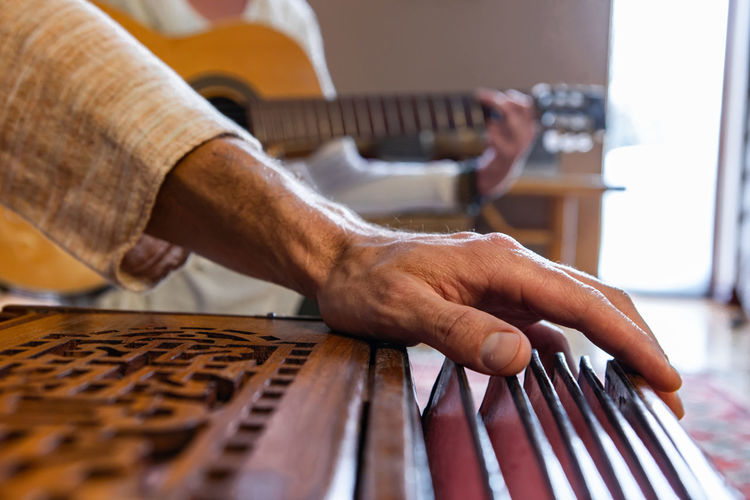 Close-up of man playing guitar on table