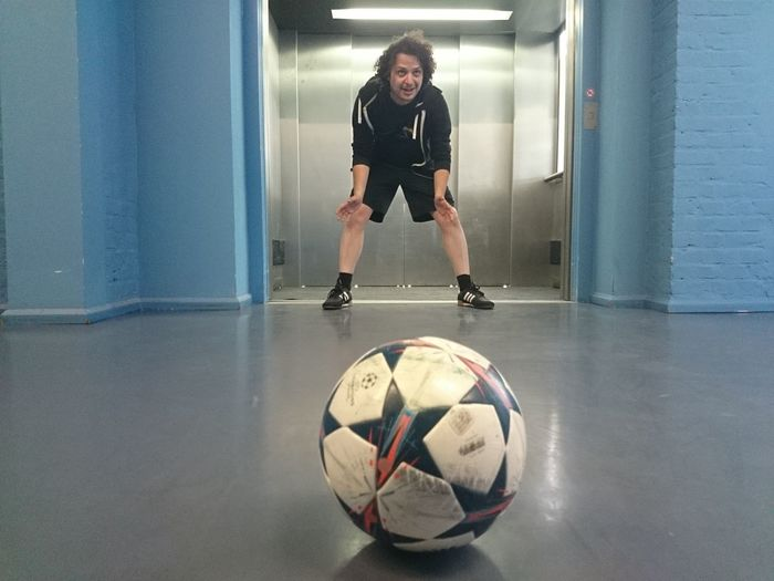 Young man playing soccer in corridor against elevator