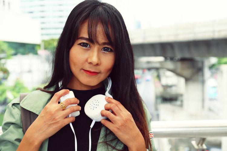 Woman wearing headphones in city