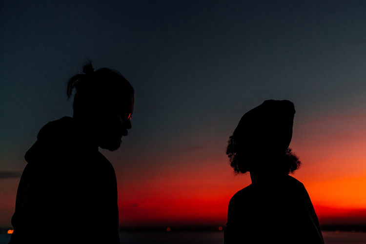 Silhouette of couple standing at beach against clear sky during sunset
