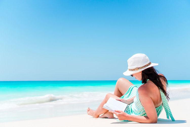 Woman reading book on beach against blue sky