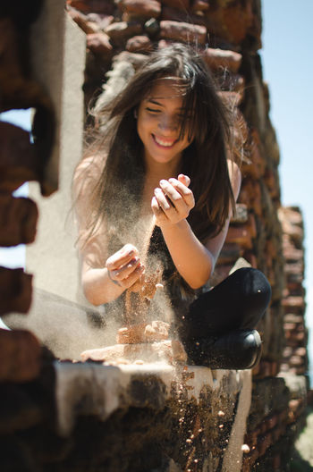 Young woman playing with sand