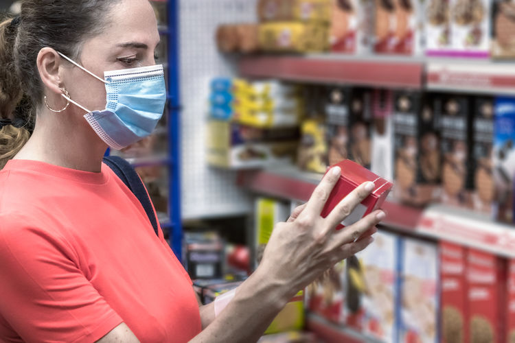 Mature woman wearing face protective mask buying groceries at supermarket.