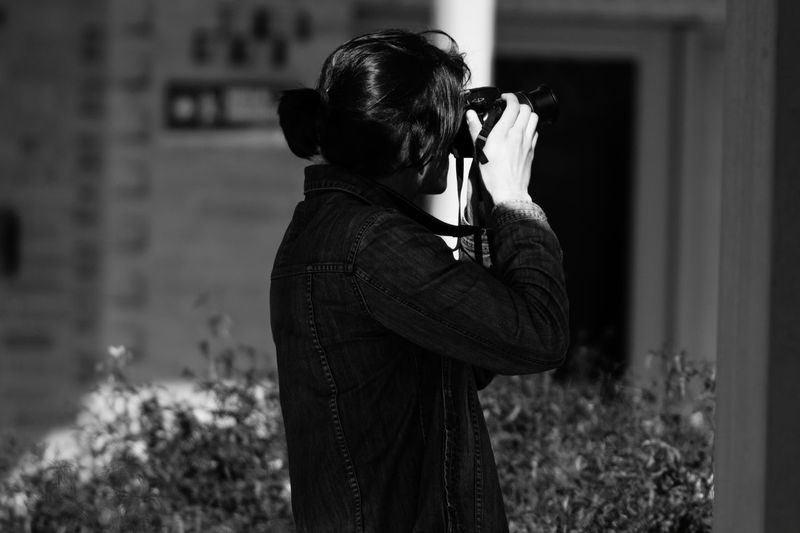Rear view of man photographing outdoors