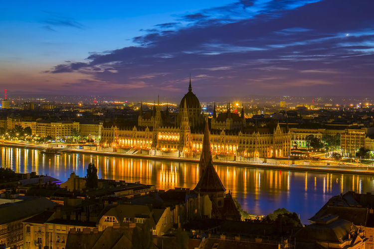 Illuminated hungarian parliament building and cityscape against sky at night