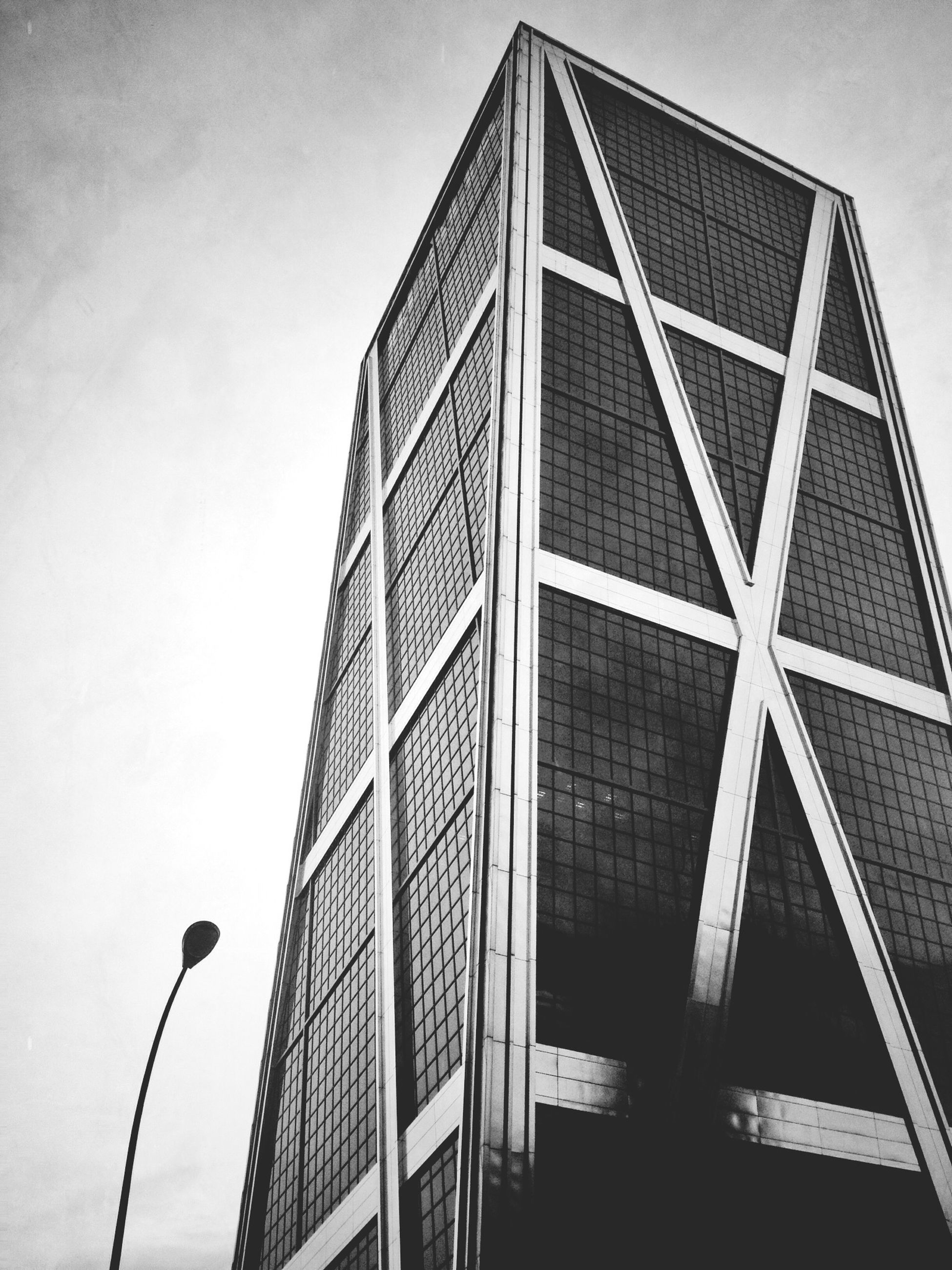 low angle view, architecture, building exterior, built structure, modern, office building, sky, building, tall - high, city, tower, skyscraper, street light, day, outdoors, glass - material, no people, window, tall, clear sky