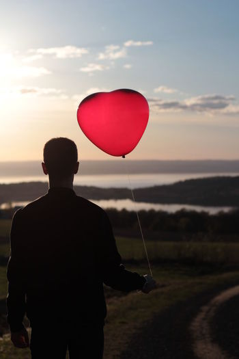 Rear View Of Man With Red Heart Shape Helium Balloon On Field