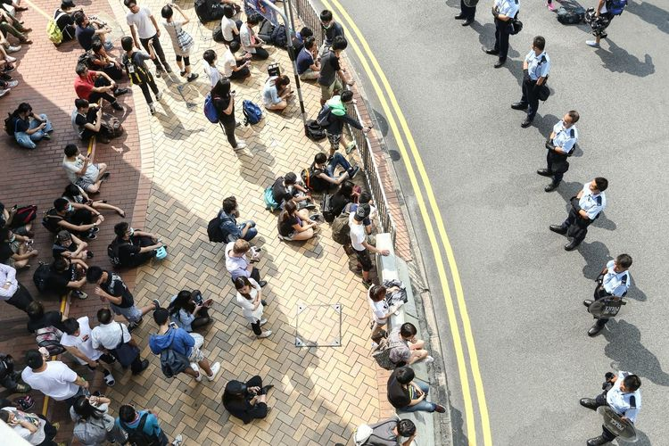 High angle view of people and police officers on street