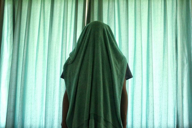 Person with towel against curtain