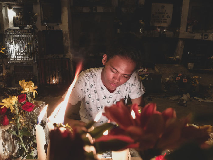 Teenage boy sitting by lit candles at home