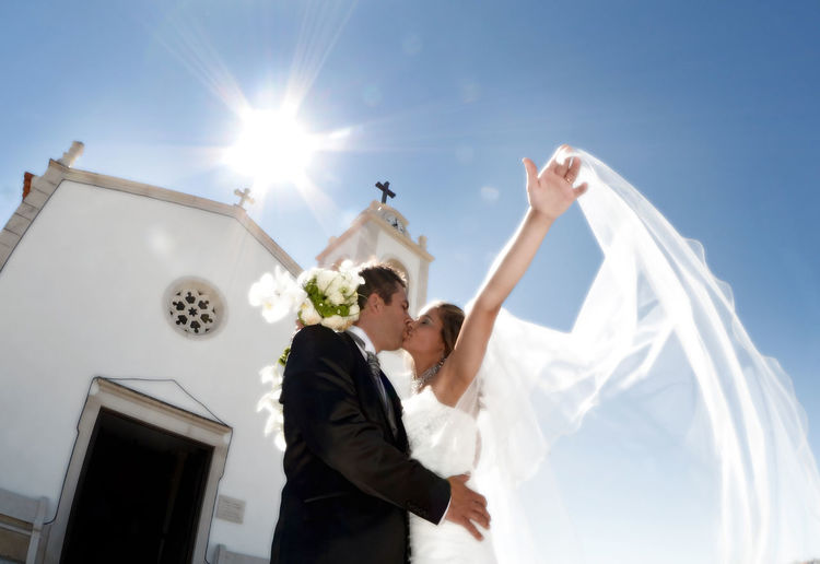 Wedding couple kissing in front of a church Architecture Bride Building Exterior Built Structure Couple - Relationship Day Lifestyles Love Low Angle View Outdoors Real People Religion Sky Spirituality Sunlight Togetherness Two People Wedding Wedding Dress BYOPaper! The Portraitist - 2017 EyeEm Awards EyeEmNewHere This Is Family
