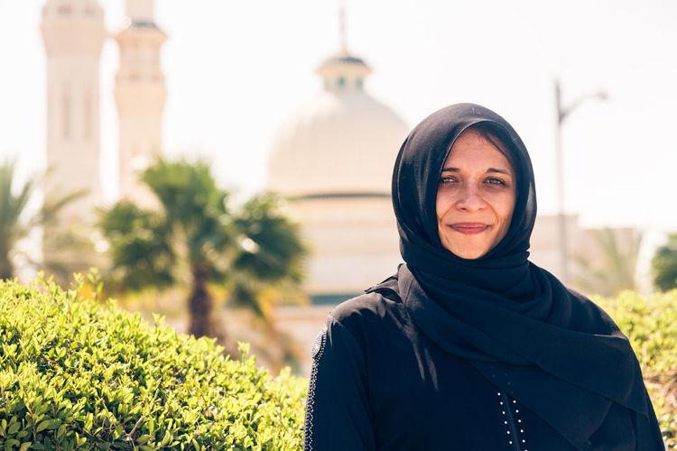 Portrait of woman wearing traditional clothing while standing against mosque