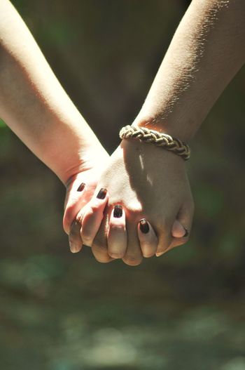 Cropped image of lesbian couple holding hands