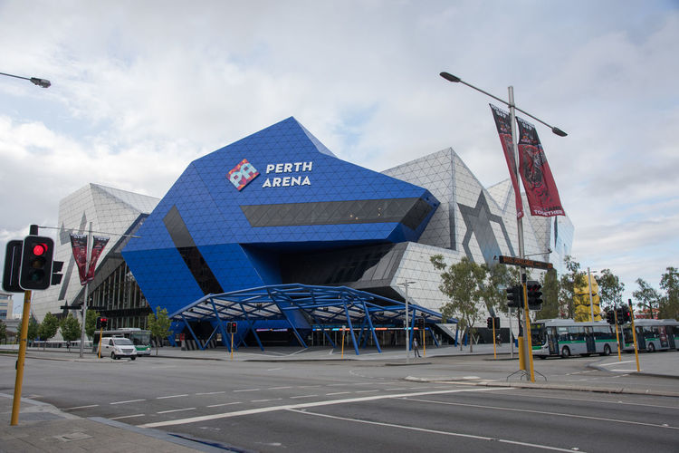 Unique architecture of the Perth Arena under a cloudy sky with transportation and yellow moving sculpture in Perth, Western Australia. Architecture Arena Arts And Entertainment Australia Blue Building Exterior Built Structure City Cloud - Sky Communication Day Geometric Geometric Shape Outdoors Perth Road Sculptural Sports Venue Street Tourist Attraction  Transportation Travel Destinations Venue Western Australia White